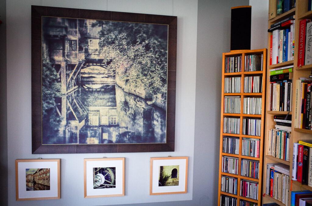 großes Bild auf Leinen, kleine Fotos auf Papier als Ensemble an einer Wand statt digital aufbewahrt.