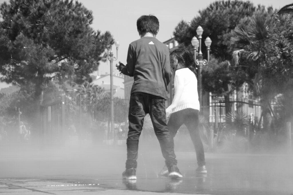 streetphotography  Nizza Plaza mit Wasserdunst und tanzenden Kindern in schwarz-weiß